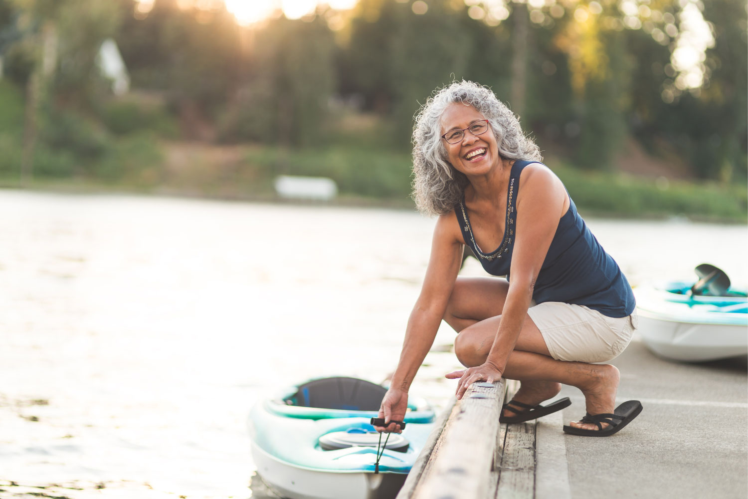 Woman with dentures smiles while holding her kayak on a lake after receiving care at Rockingham Prosthodontics