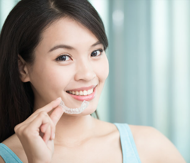 young woman holding clear aligner