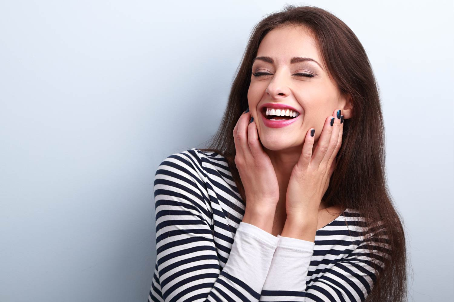 Brunette woman in a striped shirt smiles after straightening her teeth with clear aligners in Harrisonburg, VA