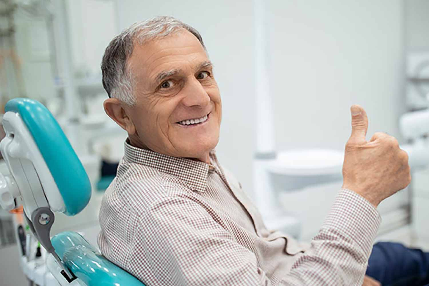 Mature man in the dental chair giving the thumbs up sign.