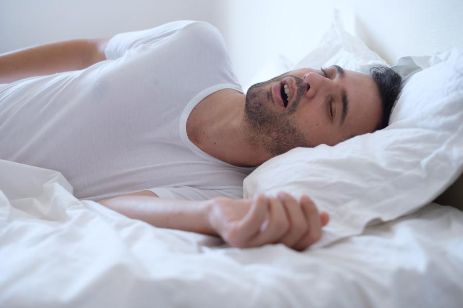 Man with obstructive sleeps apnea sleeps fitfully in white sheets