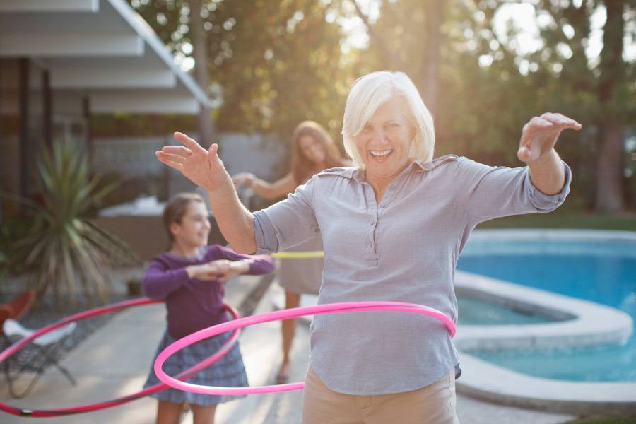 Woman smiles while hula hooping with her granddaughter after replacing missing teeth