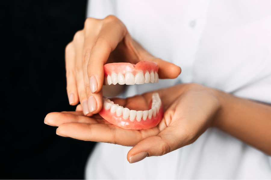 A prosthodontist holds a pair of dentures to show a patient their artificial teeth replacement
