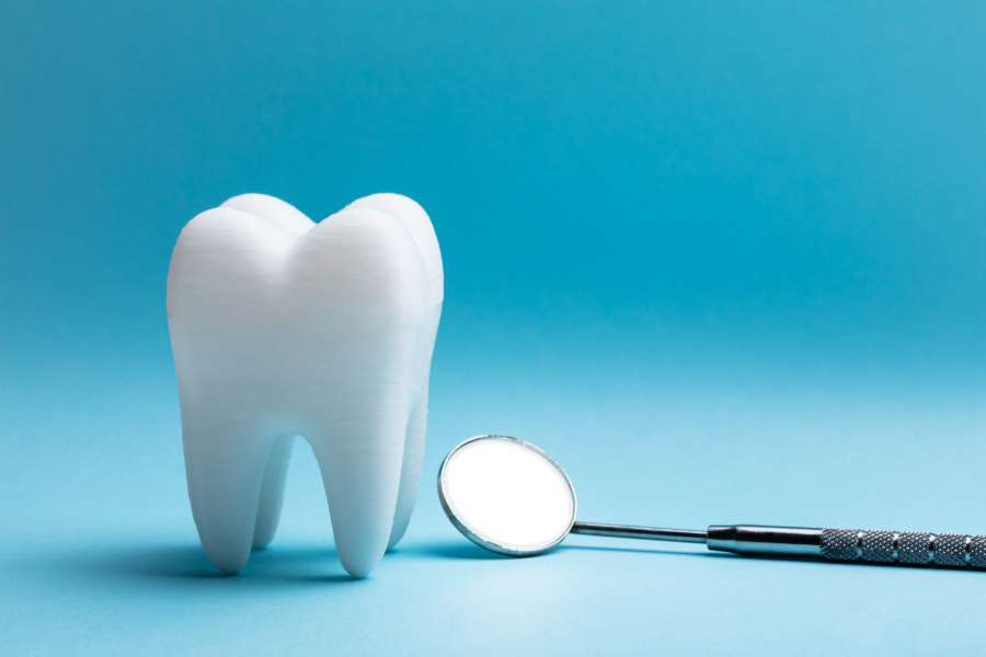 White tooth next to a special dental mirror on a blue background to symbolize a tooth extraction
